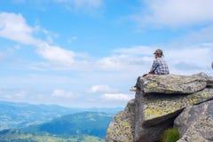 Мечтая мальчик сидит на скале на предпосылке плавая clo Стоковая Фотография