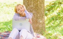 Мечта о новых работе или перестановке Ноутбук девушки мечтая в парке сидит на траве Мечта об успешном проекте r стоковое изображение