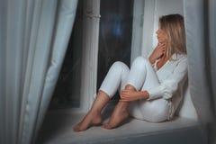 Мечты девушки сидеть на окне стоковые фото