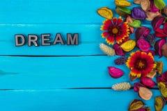 Мечт слово на голубой древесине с цветком Стоковое Изображение RF