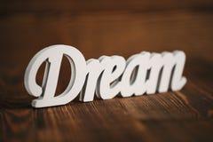 Мечт текст на деревянной предпосылке Стоковые Фото