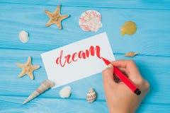 Мечт текст Шрифт помечать буквами мотивационное слово на белом холсте с красными чернилами каллиграфом Seashells и морские звезды стоковое фото rf