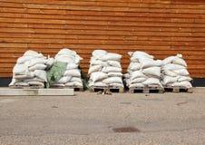 Мешки с песком в 5 кучах с деревянной стеной в предпосылке Стоковая Фотография