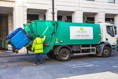 Мешки для мусора загрузки человека сборщика мусора на его тележке Стоковая Фотография