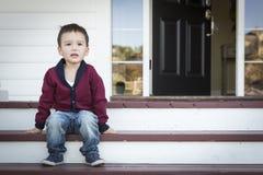 Меланхоличный мальчик смешанной гонки сидя на шагах парадного крыльца Стоковое Фото