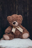 Медведь плюша сидит на подушке стоковые изображения