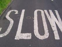 Медленный знак покрашенный на дороге Стоковые Изображения
