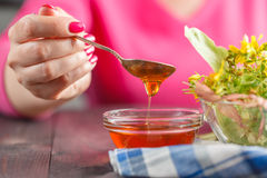 Мед женщины черпая с известк-цветением на таблице Стоковая Фотография RF