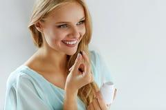 Медицина Красивая девушка принимая лекарство, витамины, пилюльки стоковое фото