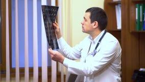 Медицина клиника Мужской доктор тщательно рассматривает рентгеновский снимок видеоматериал