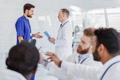 Медицинская бригада имея переговор на клинике Стоковые Изображения