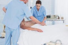 Медицинская бригада оживляя человека с дефибриллятором Стоковое Изображение RF