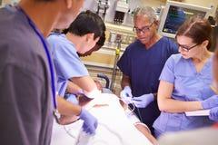 Медицинская бригада работая на пациенте в отделении скорой помощи стоковое изображение