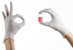 Медицинская тема: рука доктора в белой перчатке держа красную пробирку жидкости для впрыски изолированной на белой предпосылке Стоковое Фото