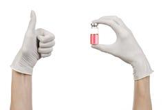 Медицинская тема: рука доктора в белой перчатке держа красную пробирку жидкости для впрыски изолированной на белой предпосылке Стоковая Фотография