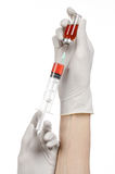 Медицинская тема: рука доктора в белой перчатке держа красную пробирку жидкости для впрыски изолированной на белой предпосылке Стоковые Изображения RF