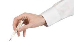 Медицинская тема: рука доктора держа термометр для того чтобы измерить температуру пациента на белой предпосылке Стоковые Изображения
