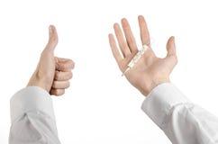 Медицинская тема: рука доктора держа термометр для того чтобы измерить температуру пациента на белой предпосылке Стоковое Изображение RF