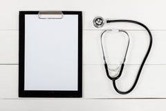 Медицинские доска сзажимом для бумаги и стетоскоп на белом деревянном столе Стоковое Изображение RF