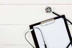 Медицинские доска сзажимом для бумаги и стетоскоп на белом деревянном столе Стоковые Изображения RF