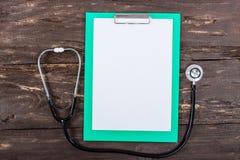 Медицинские доска сзажимом для бумаги и стетоскоп на темном деревянном столе Стоковое Изображение