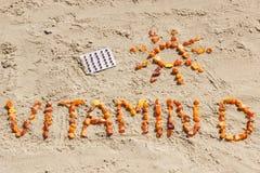 Медицинские пилюльки, Витамин D надписи и форма солнца на песке на пляже, временя и здоровый образ жизни стоковое изображение