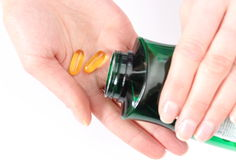 Медицинские пилюльки в руке полили от бутылки Стоковые Фото