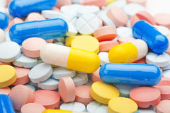 Медицинские пилюльки голубые и белые на предпосылке покрашенных пилюлек Стоковое Фото
