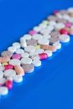 медицинские пилюльки на голубой предпосылке стоковая фотография