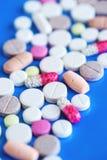 медицинские пилюльки на голубой предпосылке стоковое изображение rf