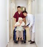 Медицинские профессионалы с пациентом в коридоре Стоковые Фото