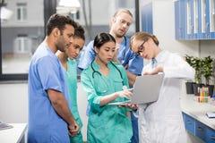 Медицинские работники используя компьтер-книжку во время обсуждения в лаборатории Стоковые Изображения RF