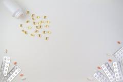 Медицинские таблетки, пилюльки в пакете волдыря и капсулы рыбьего жира омеги разливая из белой бутылки на белой предпосылке Стоковые Фото