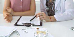 Медицинские форма, капсулы и пилюльки рецепта лежат на фоне доктора и пациента обсуждая здоровье Стоковая Фотография