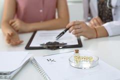 Медицинские форма, капсулы и пилюльки рецепта лежат на фоне доктора и пациента обсуждая здоровье Стоковые Изображения RF