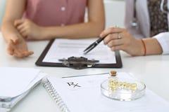 Медицинские форма, капсулы и пилюльки рецепта лежат на фоне доктора и пациента обсуждая здоровье Стоковое Изображение RF