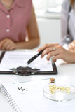 Медицинские форма, капсулы и пилюльки рецепта лежат на фоне доктора и пациента обсуждая здоровье Стоковое Фото