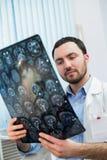 Медицинский офис - портрет средн-постаретого мужского доктора смотря развертку томографа компьютера Стоковое фото RF
