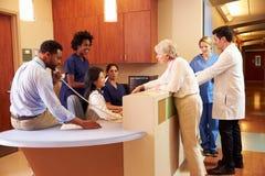 Медицинский персонал на занятой станции медсестры в больнице стоковое фото rf