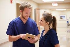 Медицинский персонал смотря таблетку цифров в коридоре больницы Стоковое Фото