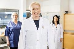 Медицинский профессионал усмехаясь пока стоящ с командой в клинике Стоковое фото RF