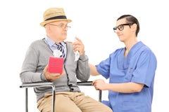 Медицинский профессионал утешая унылого старшего человека стоковая фотография