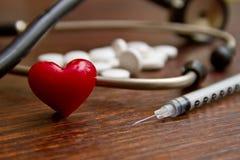 Медицинский стетоскоп и красное сердце с шприцем и пилюльками дальше Стоковые Фото