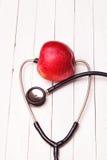 Медицинский стетоскоп и красное яблоко на белой таблице Стоковые Изображения