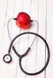 Медицинский стетоскоп и красное яблоко на белой таблице Стоковое фото RF