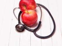 Медицинский стетоскоп и красное яблоко на белой таблице Стоковые Фотографии RF
