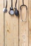 Медицинский стетоскоп на деревянной предпосылке стола Рабочее место доктора Взгляд сверху Стоковые Фото