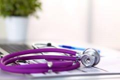 Медицинский стетоскоп около компьтер-книжки на деревянном Стоковые Изображения RF