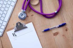 Медицинский стетоскоп около компьтер-книжки на деревянном Стоковое фото RF
