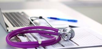 Медицинский стетоскоп около компьтер-книжки на деревянном Стоковая Фотография RF